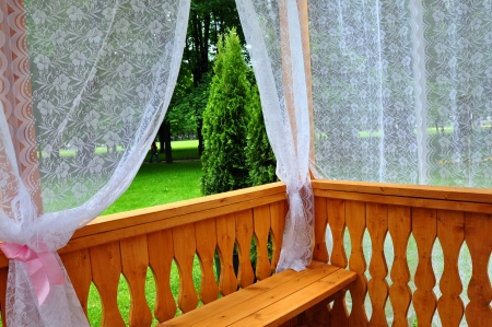 Wooden porch with lace curtains and garden view photo