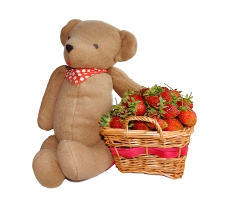 Strawberry in a basket and hand made teddy bear toy isolated on white background Stock Photo - 14480023