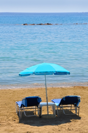 Blue deckchairs under parasol on seaside photo