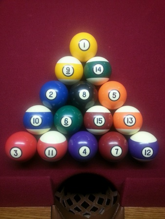 pocket: Racked pool table balls on a red pool table