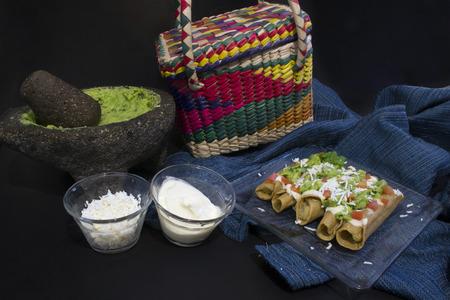Mexicaanse gouden taco's vergezeld van de complementen, typisch Mexicaans eten Stockfoto