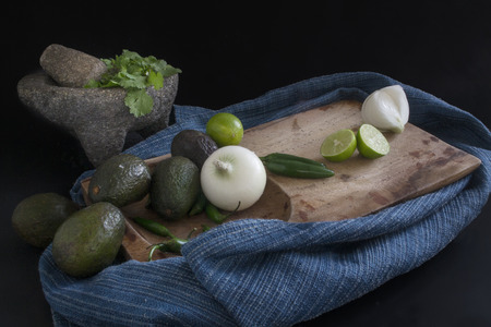 Ingredients for the preparation of guacamole or Mexican sauce, arranged on chopping board and accompanied by a molcajete