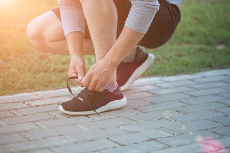 Man tying his shoes on the grass 版權商用圖片