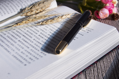 Of the books on the desk, pen, ears and flowers