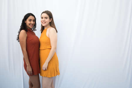 INTERRACIAL WOMEN FRIENDSHIP WITH AUTUMN COLORS DRESSES