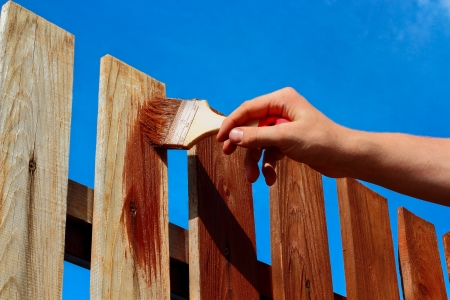 wood fence: Painting wooden fence with brown paint