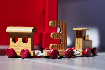 wooden  toy train on a red and gray background photo