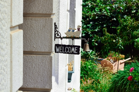 come home: Welcome sign with bell and ducks on a summer day