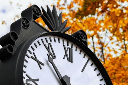 12 o'clock:  clouseup clock in the autumn park Stock Photo