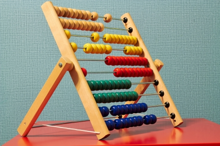 multiplication: Colourful Beaded Abacus are located  on a red table Stock Photo