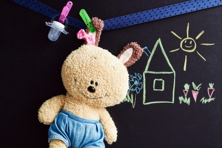soft toy: soft toy  hangs  on a rope, chalkboard with drawing   behind  Stock Photo