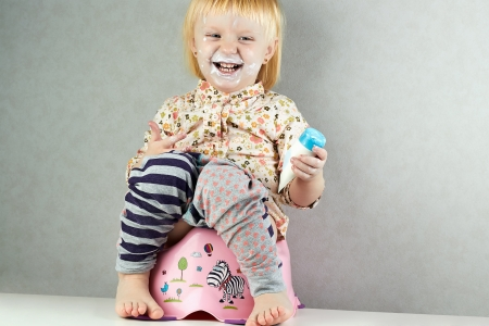 Small girl sits with a cream on her face on a potty  photo