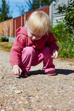 l hand: Little  blonde girl plays with pebbles in the road