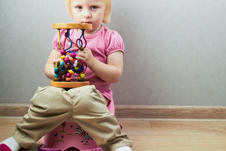 Small girl sits with a toy on a potty  photo