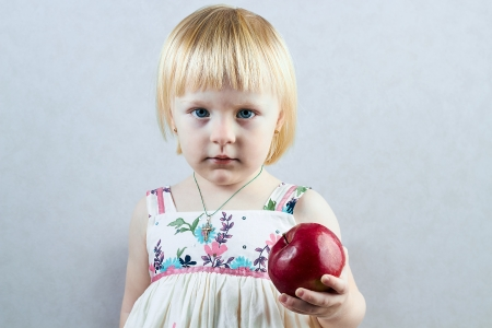 stubbornness:  Serious little girl holds  a big  red apple Stock Photo