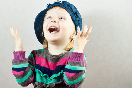 Happy little girl rises up her hands with delight Stock Photo
