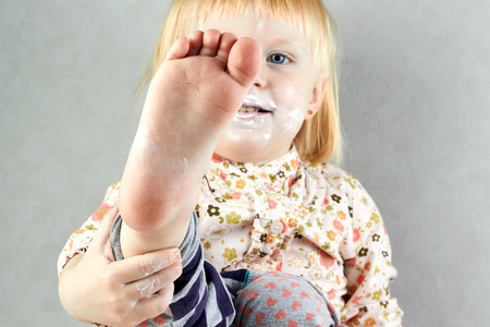 dirty blond: Little girl shows  her barefoot on a gray background Stock Photo