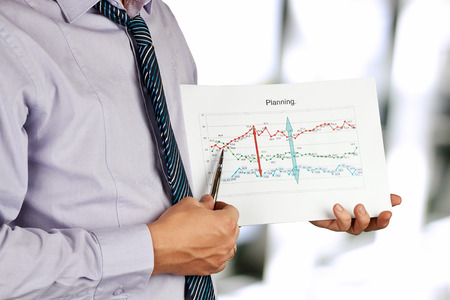 Businessman standing and showing graphics. Presentation. photo