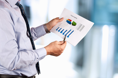 Businessman standing and showing graphics, diagram. Presentation.