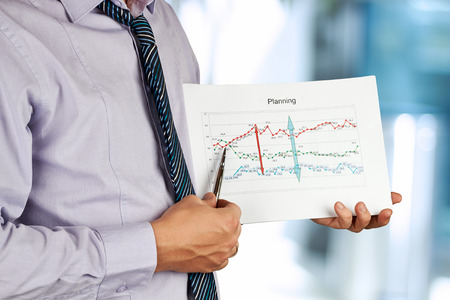 Businessman standing and showing graphic. Presentation. photo