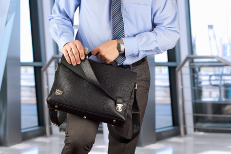 Businessman holding and opening  a  leather briefcase photo