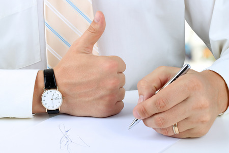 Businessman  signing a document  by pen and showing OK sign with his thumb up   photo