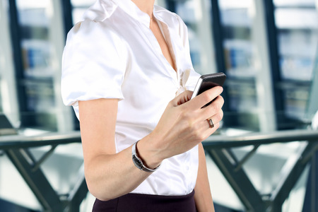 Businesswoman holding  and using the  mobile  smart  phone  photo
