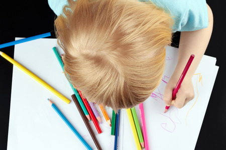 Small blond girl is drawing by pencils  Top view   photo