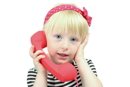 Pretty  little blond girl with a red  retro phone  photo