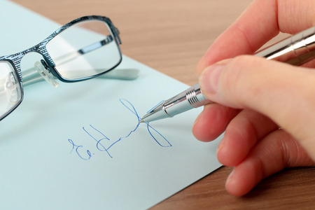 conclude: Business worker signing the contract to conclude a deal. Glasses is behind Stock Photo