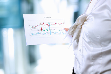 oncept:  Well-dressed businesswoman standing and showing graphic. Presentation. Stock Photo