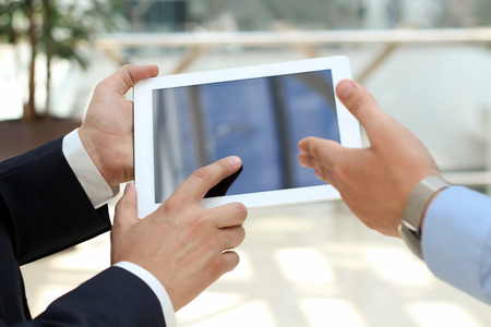Image of two young businessmen using touchpad photo