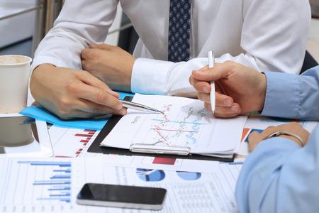 collega's samen te werken en analyseren van financiële cijfers op een grafieken Stockfoto