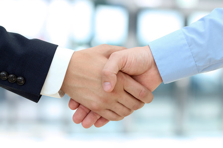 business handshake: Close-up image of a firm handshake  between two colleagues in office.