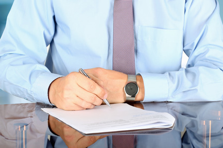 Businessman  sitting at office desk and  signing a contract  by pen photo