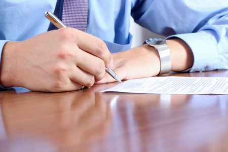 Great: Businessman  sitting at office desk and  signing a contract  by pen