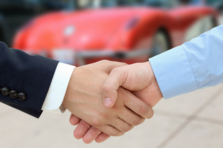 showroom: Close-up image of a firm handshake  after a successful deal of buying a car