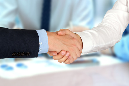 Close-up image of a firm handshake  between two colleagues in  the office. photo