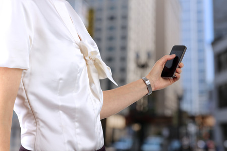 Businesswoman holding  and using the  mobile  smart  phone. Modern city behind photo