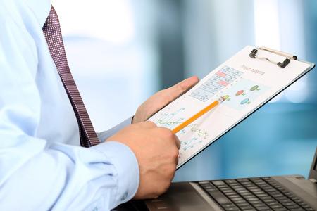 empleados trabajando: hombre de negocios sentado delante de la computadora port�til, el an�lisis de datos en gr�ficos en la oficina
