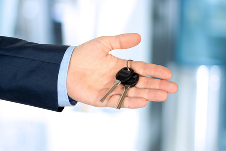 Cropped image of estate agent giving house keys in office photo