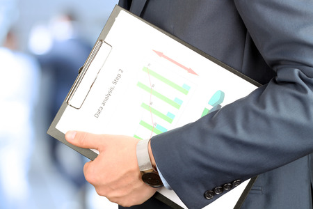 oncept: Businessman standing and holding  graphic in his hand . Business people behind Stock Photo