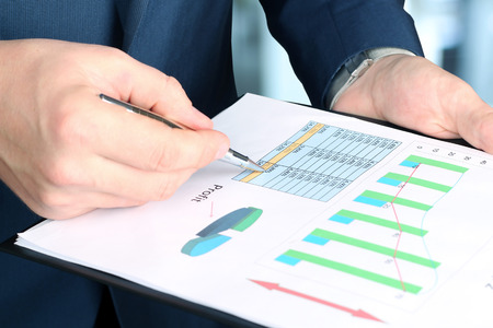 oncept: Businessman standing and showing graphics, diagram. Presentation.