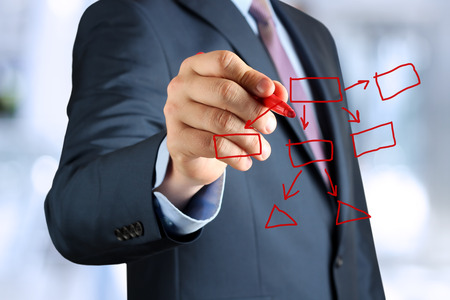 man in a business suit makes a block diagram on a blackboard photo