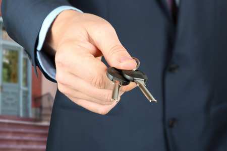 trade secret: Cropped image of estate agent giving house keys in office