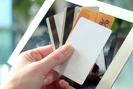 debet: Young business woman holding   credit cards . On-line shopping on the internet using a tablet Stock Photo