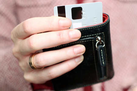 Woman get  out a credit card from  black purse in the shop photo