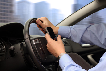 businessman using mobile smart phone while driving the car Stock Photo