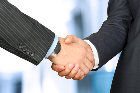 Close-up image of a firm handshake between two colleagues in office. photo