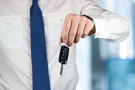 ownership and control: Young successful businessman offering a car key. Close-up of driver Stock Photo
